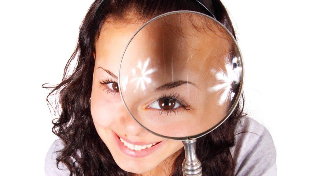 虫眼鏡を通してなにかを確認する女性